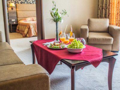 Маса със закуска, дивани и легло в хотелска стая