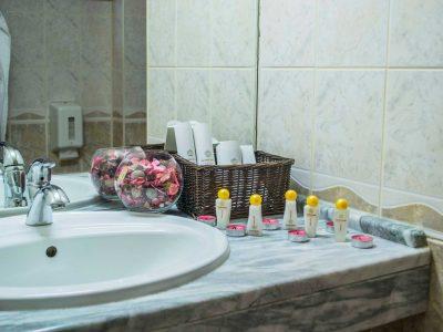 Тоалетни принадлежности, свещи и мивка в хотелска баня