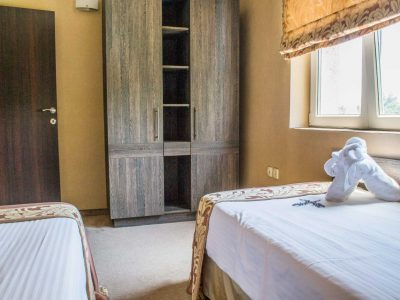 Две единични легла и шкаф за дрехи и принаджелности в хотелски апартамент