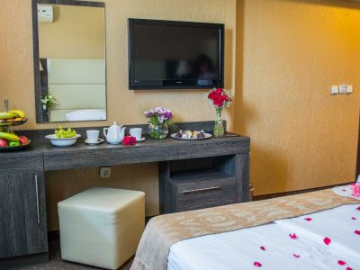 Рози, плодове, телевизор, огледало и легло в хотел