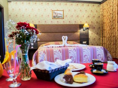 Закуска от кифлички, кроасани и кафе украсени с цветя гледащи към легло в хотел