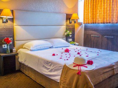 Шапки и рози върху легло в хотел двореца