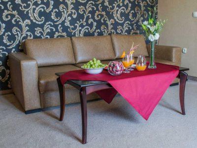 Плодове, натурален сок и украса с цветя върху маса пред диван в хотелска стая