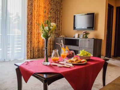 Сандвичи, плодове и натурален сок върху маса в хотелска стая