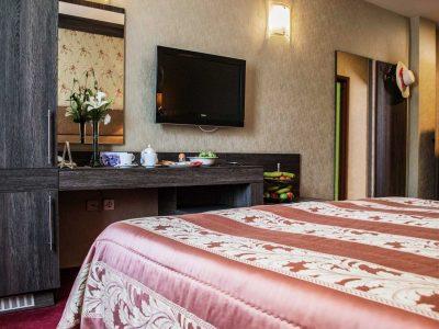 Телевизор и закуска гледащи към легло в стая на хотел
