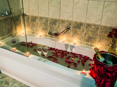 Вана с рози, шампанско и свещи в хотелски апартамент в хотел Двореца