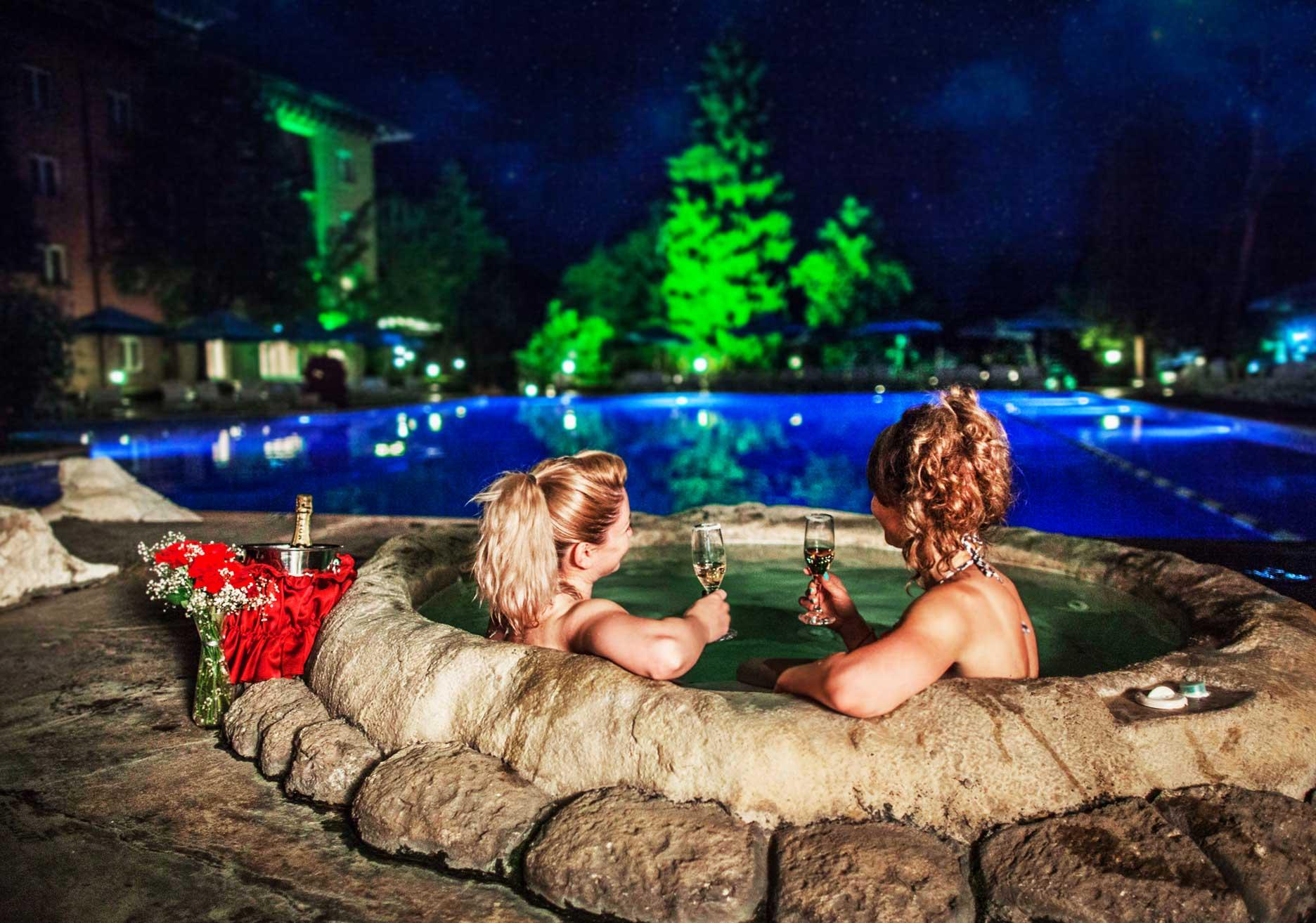 Две жени пиещи шампанско във външно джакузи
