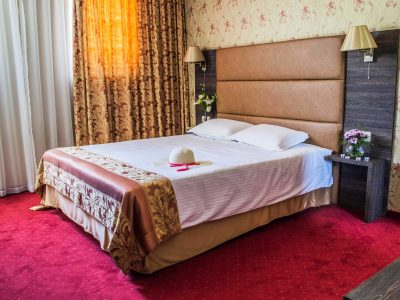 Шапка върху легло с украса от цветя в единична хотелска стая Двореца