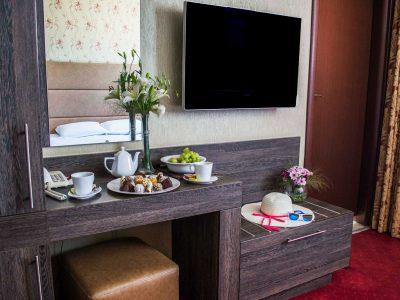 Шапка върху рафт, телевизор, украса от цветя и домашни сладки в хотелска стая