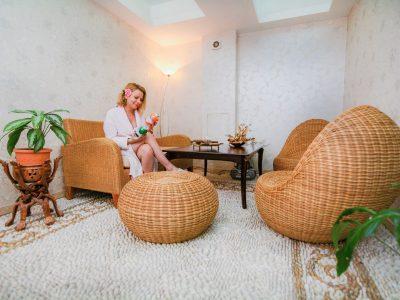 Жена разглеждаща спа продукти в релакс стая