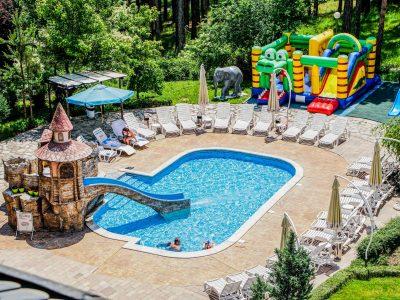 Детски басейн, пързалка, шезлонги, надуваем замък в слънчев ден
