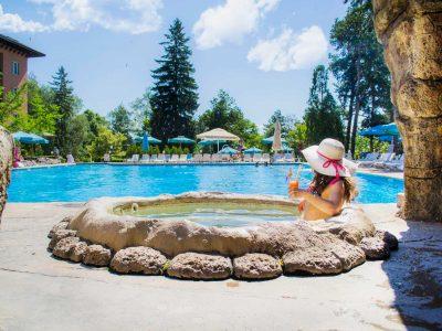 Жена по бански в джакузи пиеща коктейл и гледаща към минерален басейн в слънчев ден