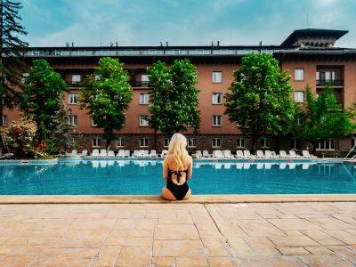 момиче седи до басейн пред хотел